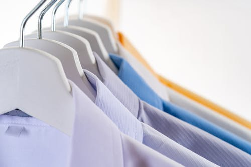 Collection of colorful similar formal shirts hanging on rail in shop against white wall