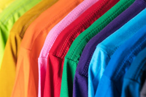 Closeup of multicolored vibrant cotton t shirts hanging in row in modern wardrobe
