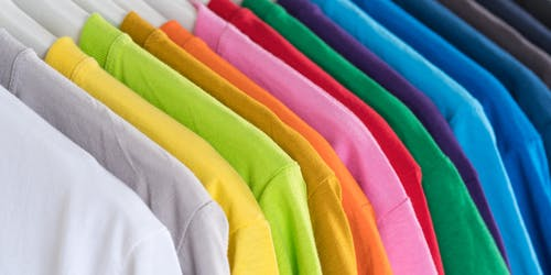 Stack of multicolored t shirts on hangers