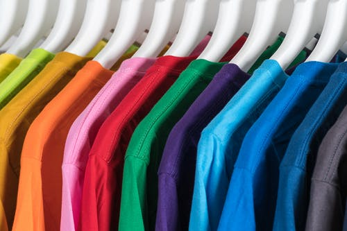 Hangers with colorful cotton t shirts in wardrobe