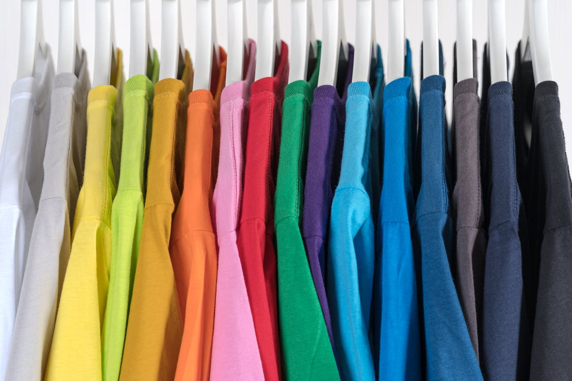 Selection of colorful bright fashionable t shirts hanging on rack in store against white background