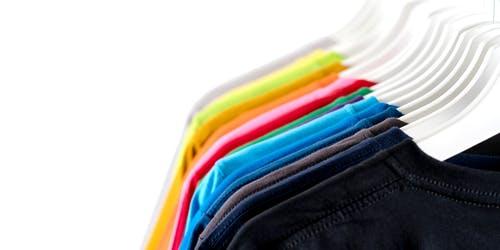 Trendy multicolored garments hanging on rack against white background