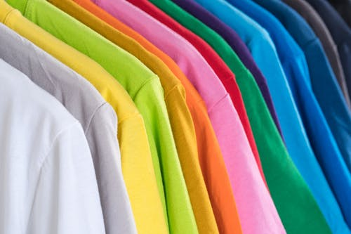 Organized multicolored clothes hanging on rack