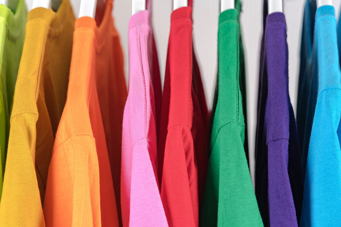 Collection of colorful cotton t shirts on hangers in store