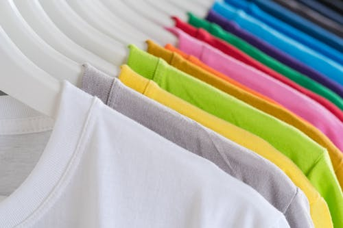 Closeup bright multicolored soft cotton t shirts hanging on rail in well organized wardrobe