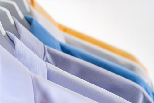 Details of various stylish formal shirts hanging in row on rack against white background