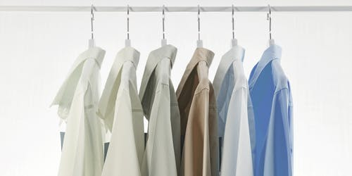 Collection of minimalist classic shirts hanging on rail in modern fashion boutique against white background