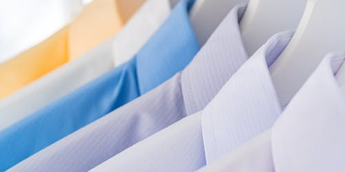 Contemporary style assorted bright shirts with ironed collars on racks in clothing store
