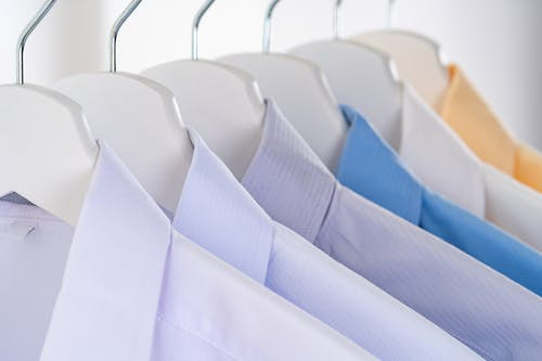 Different elegant shirts for men with collars hanging on identical racks in clothing store on white background