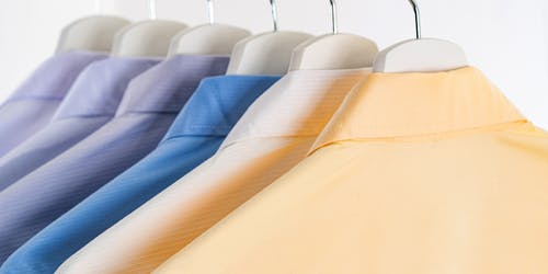 Row of bright male shirts with collars on hangers in clothing store on white background