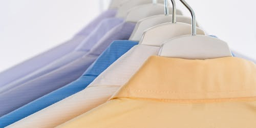 Assorted shirts hanging on hangers on rack
