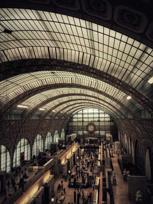 From above of people inside spacious Orsay Museum with exhibits of paintings and sculptures