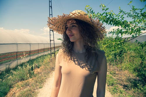 Woman in Brown Sun Hat and Brown Dress Standing Near Green Plants
