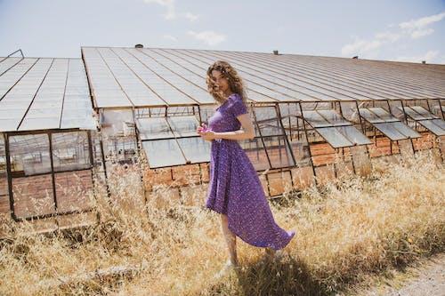Woman in Purple Dress Standing on Brown Grass Field