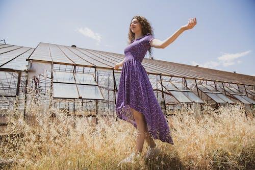 Girl in Purple Dress Standing on Brown Grass Field