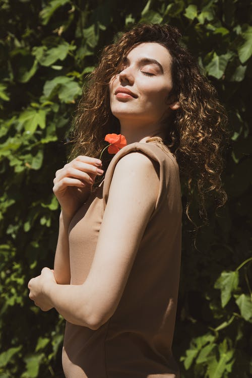 Woman in Brown Tank Top Holding Red Rose