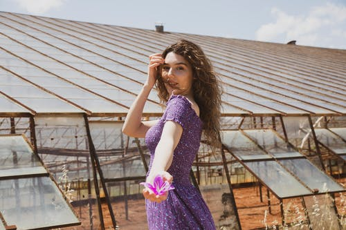 Woman in Purple Sleeveless Dress Standing on Brown Wooden Bridge