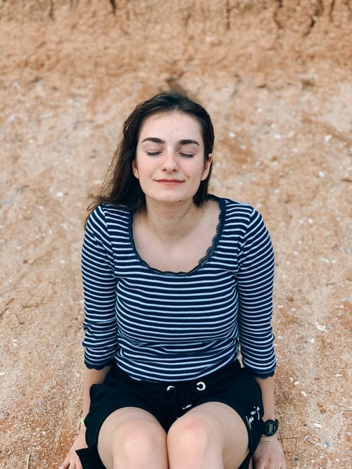 Delighted young woman sitting on stony ground