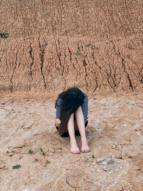 Full body of female hiding face while sitting with head on knees and resting in nature