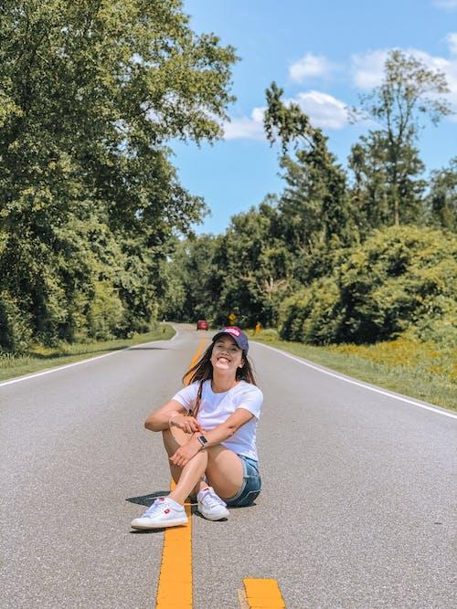 Female smiling and sitting on asphalt roadway
