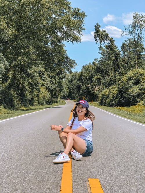 Full length of smiling young female enjoying summertime while sitting on asphalt road and laughing