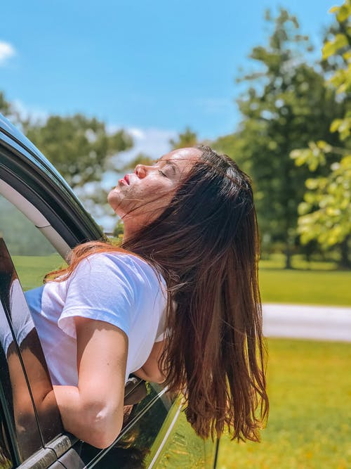 Calm woman pulled half of body out of car window