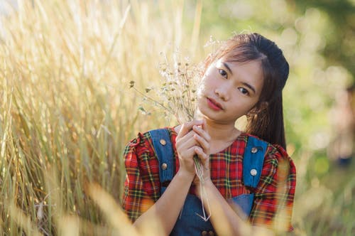 Calm Asian adolescent with bunch of flowers in long meadow grass looking at camera