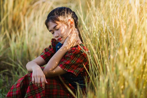 Calm girl touching neck sitting in meadow grass