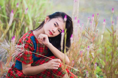 Young Asian woman sitting in grass
