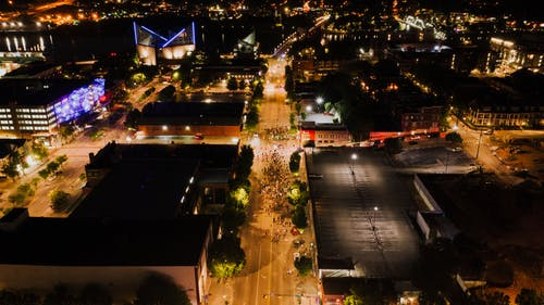 Aerial view of glowing city streets of modern town with crowd of people walking on roadway
