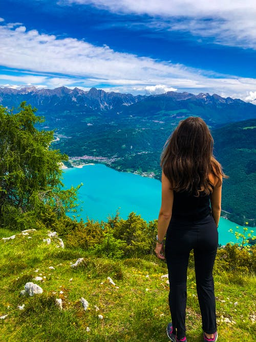 Woman admiring view of mountains and colorful lake