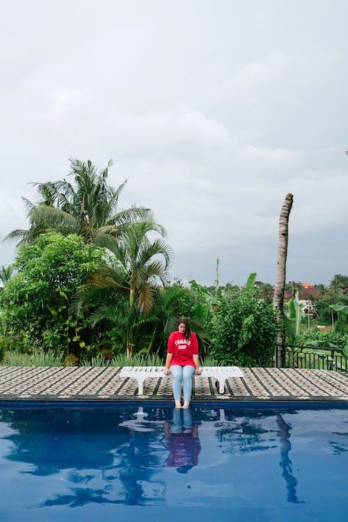Woman dipping feet in swimming pool water at resort
