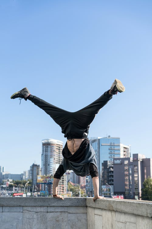 Unrecognizable male rooftopper standing upside down grabbing at roof edge while performing dangerous tricks in modern city on clear day