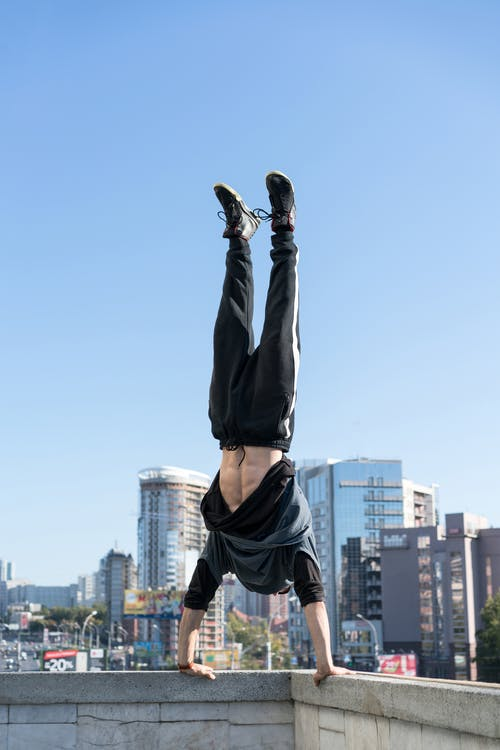Brave rooftopper doing handstand on roof edge