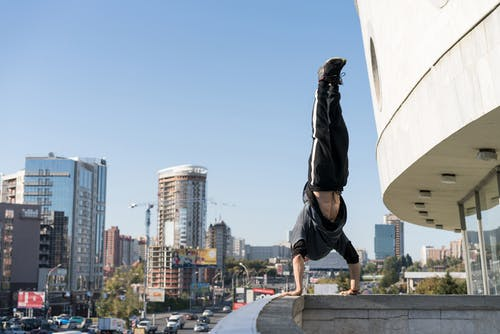 Daredevil thrill seeker doing handstand on roof edge in modern city