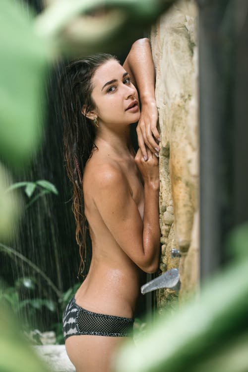 Side view of young topless brunette in bikini pants leaning with breasts on stone wall in shower of spa resort hotel