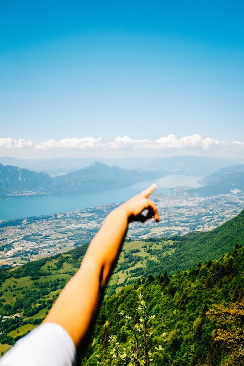 Person Pointing at Green Mountains