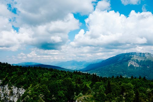 Green Trees and Mountains Under White Clouds and Blue Sky