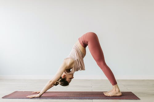 A Woman in Downward Facing Dog Yoga Position