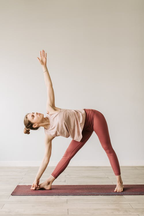 A Woman in Tank Top and Legging Side Bending