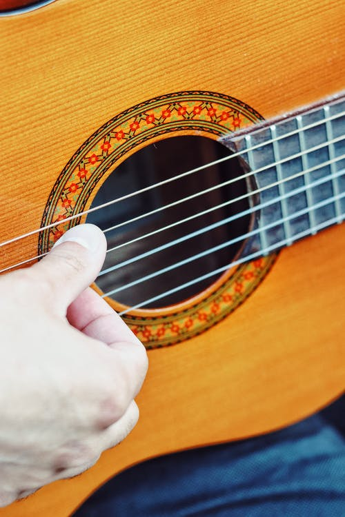 High angle of crop unrecognizable player playing melody on acoustic guitar during music practice