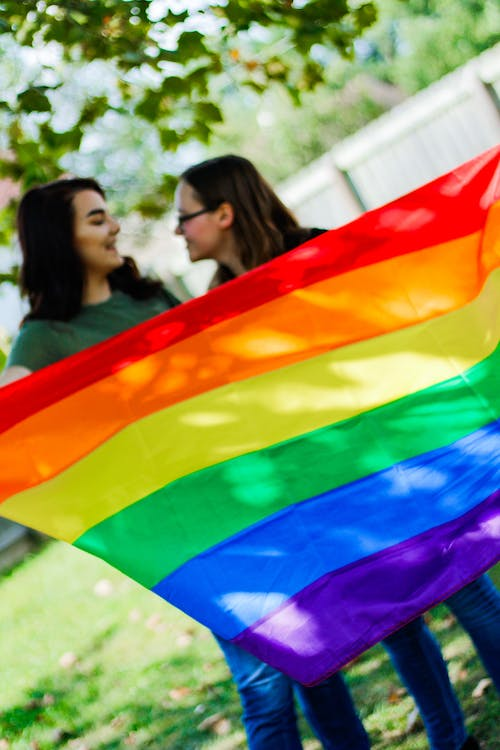 Female lovers demonstrating LGBT pride flag