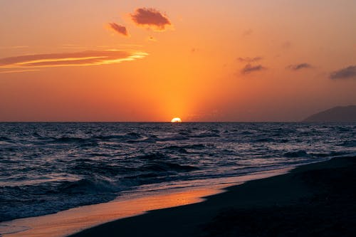 Vivid evening red sky covered with clouds above sun on horizon of wavy endless sea