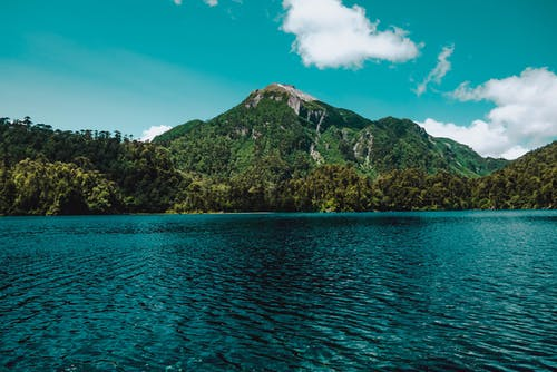 Green and Brown Mountain Beside Blue Sea Under Blue Sky