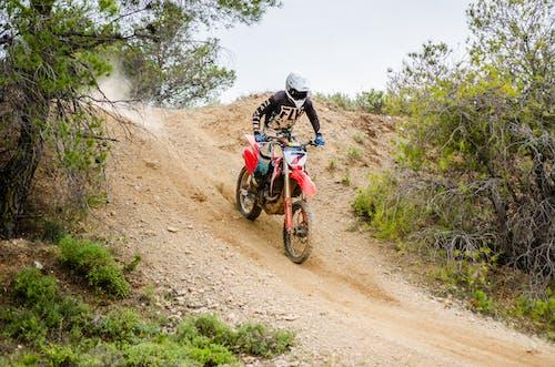 Unrecognizable motorcyclist riding down hill