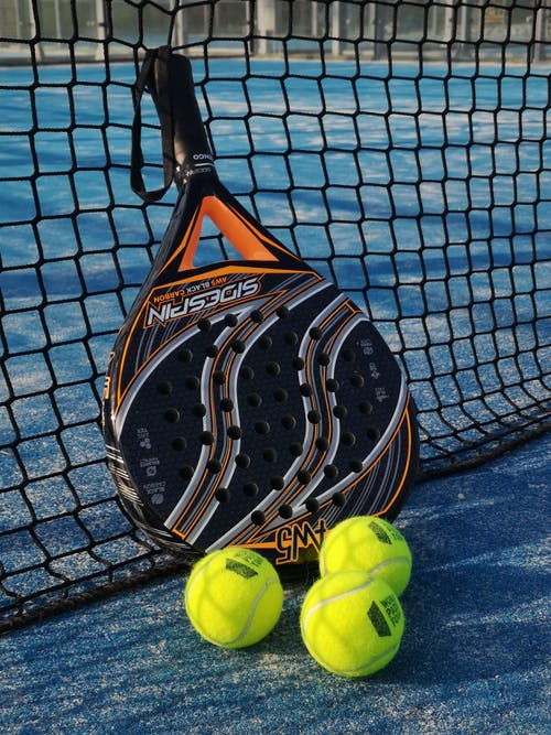 Padel racket and bright balls on tennis court