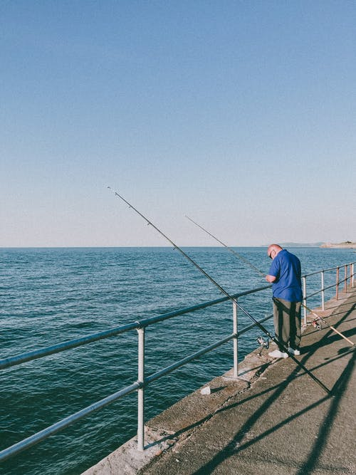 Man in Blue Shirt and Black Pants Fishing on Sea