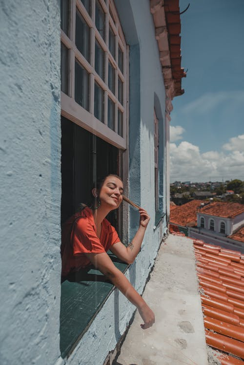 Woman in Red Shirt Leaning on Wall