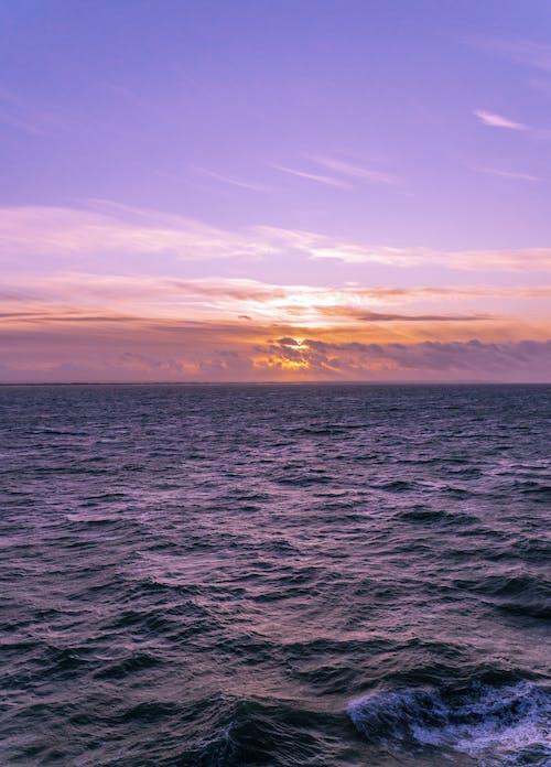 Wavy endless sea under cloudy sky at bright sundown