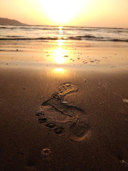 Footprint on sandy sea shore under glowing sky at sundown
